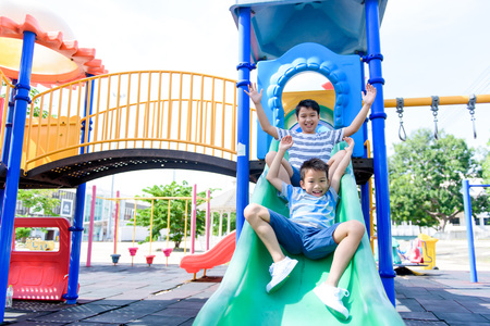 Young asian Thai boy climb to slide on the color full slider playground during summer Фото со стока