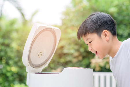 Young asian Thai boy and electric rice cooker that cooking a very good smell jasmine rice variety at home garden.