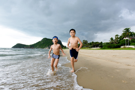 Two young Asian Thai boy play running on the beach during before the cloud storm comming with heavy rain.