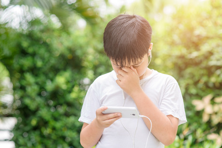 Young Asian Thai boy using a smartphone to play game and listen to music without care the surrounding and he has a problem with headache and eye pain.