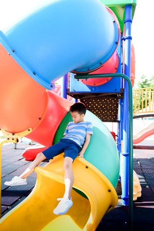 Young asian Thai boy climb to rest on the color full slider playground during summer