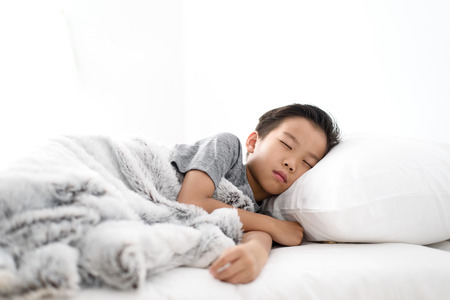 Selective focus at Young Asian Thai boy sleeping on a white bed in a bedroom.