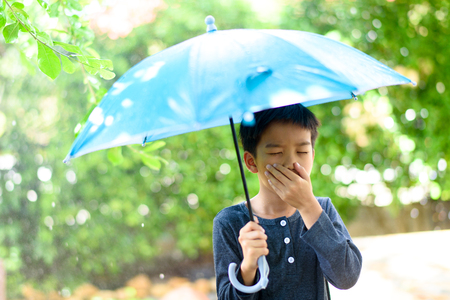 Young boy with blue umbrella get cough and feel not good under the rain in a garden. Stock fotó