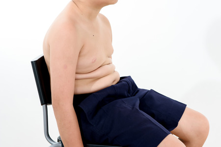 Selective focus Unhealthy fat boy on sit on white background Stock Photo