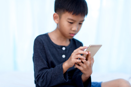 Selective focus at young Asian boy hand using a smartphone to play game with internet connection. Фото со стока