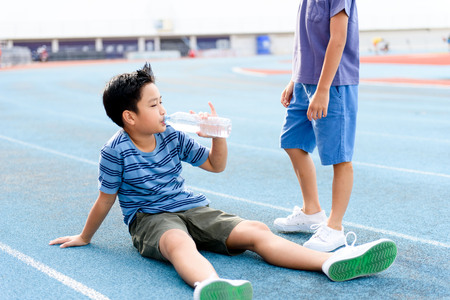 Young Asian Thai boy drinking water from bottle during resting on the blue track after running Archivio Fotografico