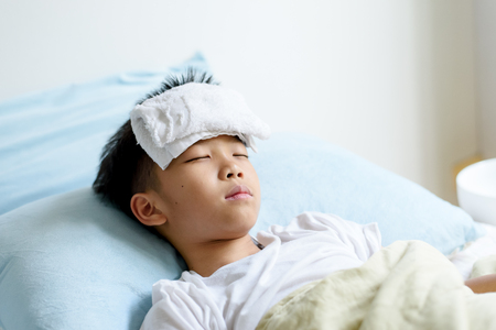 Selective focus at young Asian Thai boy sick and take rest and sleep on a bed in. 版權商用圖片