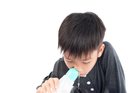 Young boy use saline water to clean his nasal on white background.
