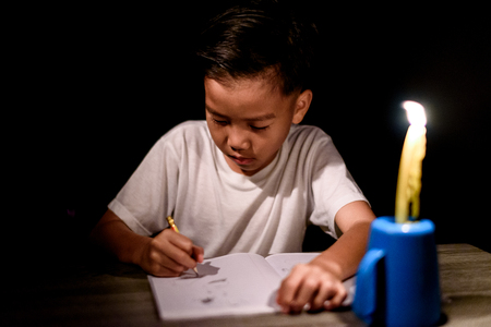 Young Asian poor boy do homework under a candle light without electricity.