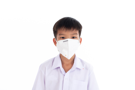 Young Thai boy put a mas on his face to protect a dust in a pollution air. 版權商用圖片