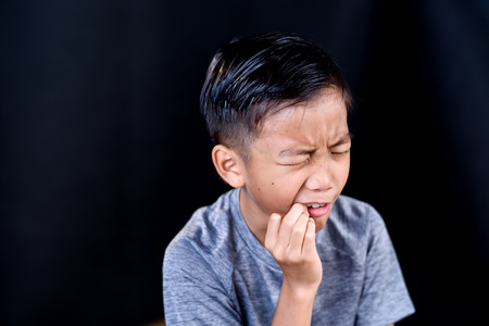 Young Asian boy feel tooth ache and unhappy on black background 版權商用圖片