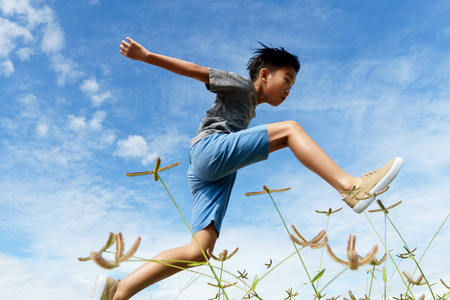 Young boy run and jump over a weeds during blue sky in summer. 版權商用圖片