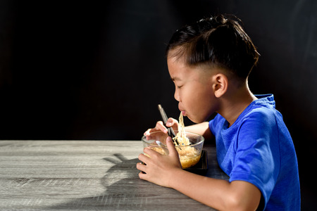 Young Asian Thai boy eat instant noodle in a glass bowl on black backgound. 版權商用圖片