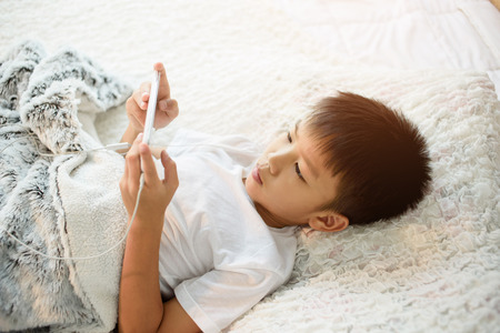 Preteen Asian Thai boy using a smartphone to play game and listen to music without care the surrounding on a white bed.