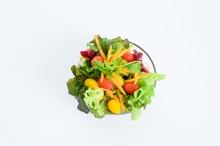 Mix of vegetable salad in glass bowl on white background