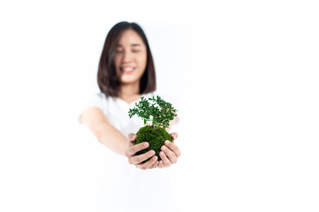 Selective focus at young Asian Thai woman carry little seeling plant. Earth day concept. Imagens - 120420497