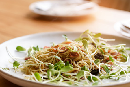 Selective focus at spaghetti with sunflower seedling salad. 版權商用圖片