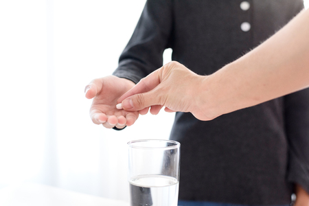 Close up a white pill for painkiller on young boy hand with a glass of water.