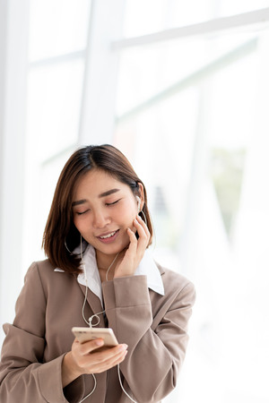 Young Asian woman use a smartphone to listen to music to relax during work in an office.