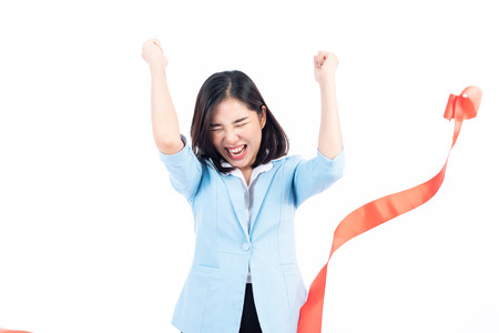 Young Asian Thai woman happy when reach a finish red ribbon line. Competition and success concept. 版權商用圖片