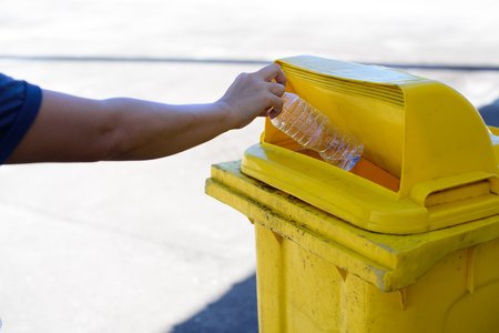 Young Asian boy drop a plastic water bottle in a yellow bin.