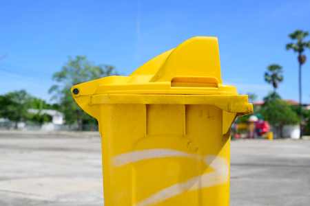 Close up yellow plastic bin under blue sky