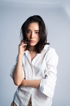 Shooting studio portrait of young Asian Thai woman with white shirt on white background. Relax and mordern concept. Imagens - 123422070