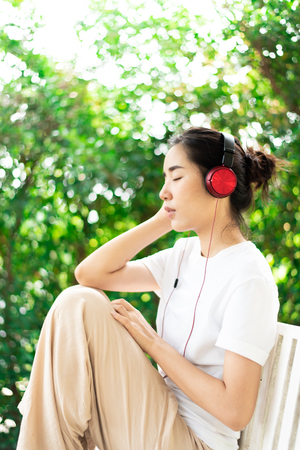 Young Asian Thai woman listen to music from headphone and relax at home. 版權商用圖片