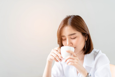 Young happy Asian woman in a work office drinkg a cup of coffee 版權商用圖片