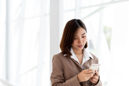 Young Asian woman use a smartphone in an office.