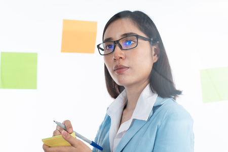 Young Asian Thai woman use the sticky note to write and create idea and post on a transparent board.