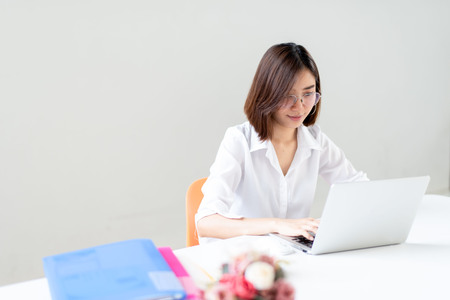 Young happy Asian woman working in a white office with laptop.