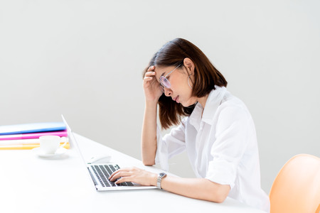 Young unhappy Asian woman working in a white office with computer laptop with stress and headache.