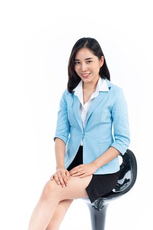 Young Thai woman in business dress sit on a chair on white background. 写真素材