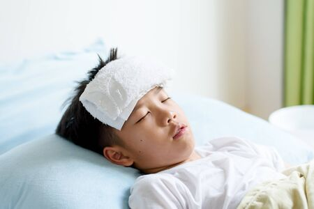 Selective focus at young Asian Thai boy sick and take rest and sleep on a bed in. Banque d'images - 131653569