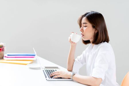 Young happy Asian woman in a work office drinkg a cup of coffee Imagens