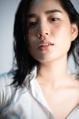 Focus at lip of young Asian Thai woman with white shirt on white background. Relax and mordern concept portrait studio.