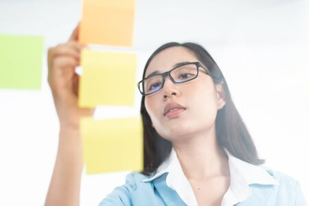Young Asian Thai woman use the sticky note to write and create idea and post on a transparent board. Imagens