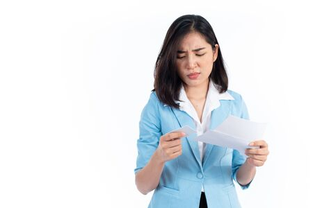 Young Asian Thai woman looks unhappy with credit card and statement.