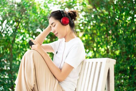 Young Asian Thai woman listen to music from headphone and relax at home. Imagens
