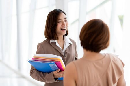 Two young Asian woman has a meeting in an office. Imagens