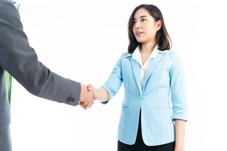 Selective focus at Young Thai business woman shaking hand with businessman in formal meeting on white background.