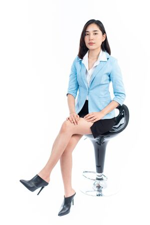 Young Thai woman in business dress sit on a chair on white background. Imagens