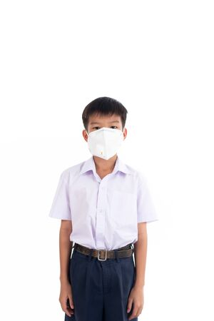 Young Thai boy put a mas on his face to protect a dust in a pollution air. Imagens