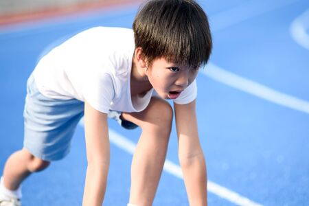 Young Asian boy prepare to start run on a blue track in summer day Imagens