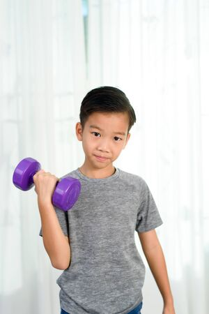 Young Asian boy train by lift drumbell by his strong arm in a bedroom at home.