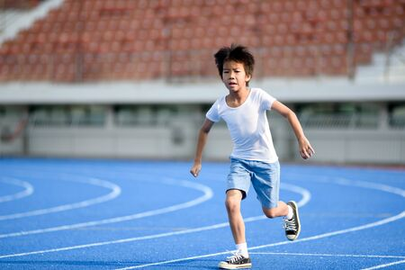 Young Asian boy run on a blue track in summer day Imagens