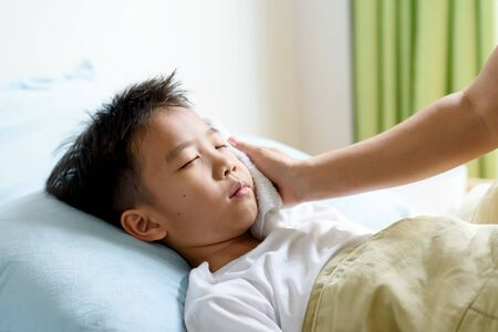 Young boy sick and sleep on a bed taking care by his mom in a bedroom.
