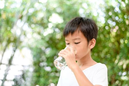 Young boy drink water from a glass in a garden. Imagens