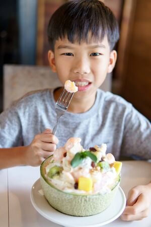 Young Asian boy eat melon mix with fruit salad